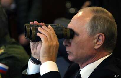 Russian President Vladimir Putin watches a military exercise at a training ground at the Luzhsky Range, near St. Petersburg, Sept. 18, 2017.