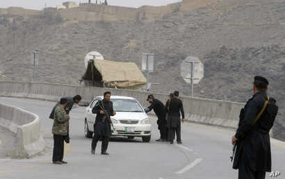 Pakistani police officers stand guard while their colleagues searching a car at a checkpoint on the highway leading to Torkhum, a border crossing between Pakistan Afghanistan, March, 20, 2017. Pakistan's prime minister recently ordered the reopening ...