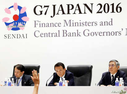 Japan's Finance Minister Taro Aso, center, and Bank of Japan Governor Haruhiko Kuroda, right, attend a news conference after the G-7 finance ministers and central bankers meeting in Sendai, Miyagi prefecture, Japan, May 21, 2016.