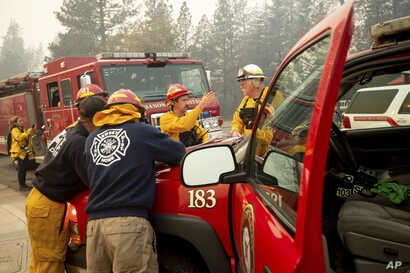 Firefighters plan their operations while battling the Camp Fire in Paradise, Calif., Nov. 10, 2018.
