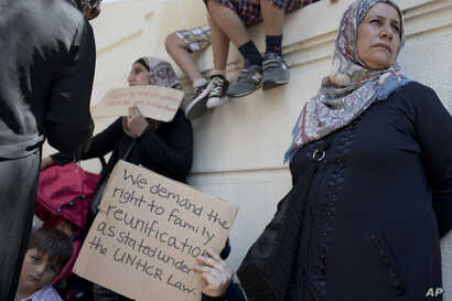 FILE - Stranded migrants and refugees hold placards as they protest outside the German Embassy in Athens.