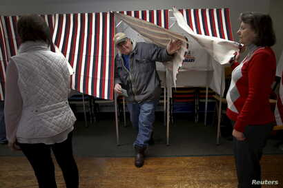 A voter exits a voting booth after filling out his ballot in the U.S. presidential primary election in the village of Groveton, New Hampshire, Feb. 9, 2016.