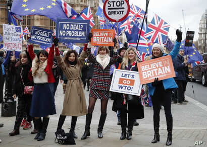 Leavers hold up signs next to pro-European demonstrators protesting opposite the Houses of Parliament in London, Jan. 15, 2019.