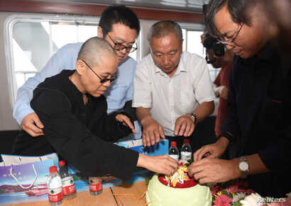 Liu Xia, wife of deceased Chinese Nobel Peace Prize-winning dissident Liu Xiaobo and other relatives attend his sea burial off the coast of Dalian, China, in this photo released by Shenyang Municipal Information Office July 15, 2017.
