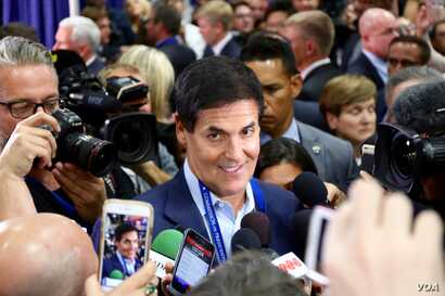 Billionaire Mark Cuban walks through the media filing center at Hofstra University, just prior to the first presidential debate in Hempstead, New York (B. Allen/VOA)