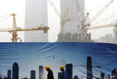 Workers walk past a billboard display showing a scene of Central Business District, as capital city skylines are shrouded with pollutant haze in Beijing, China, Nov. 9, 2015.