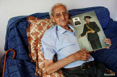Gumersindo Cubo, 101, poses for a portrait with a picture of himself when he was young, in his home in Casavieja, Avila, near Madrid, Spain, July 12, 2016.