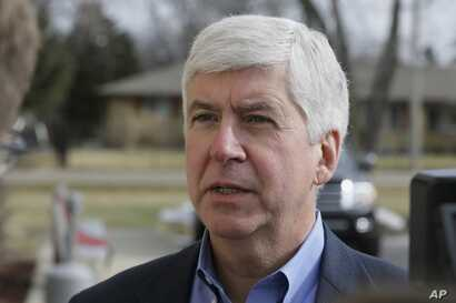 FILE - Michigan Gov. Rick Snyder is interviewed after visited a church that's distributing water and filters to its predominantly Latino parishioners in Flint, Michigan, Feb. 5, 2016.