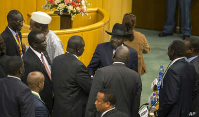 South Sudan's rebel leader Riek Machar, center-left with back to camera, shakes hands with South Sudan's President Salva Kiir, center-right wearing a black hat, after lengthy peace negotiations in Addis Ababa, Ethiopia, Aug. 17, 2015.