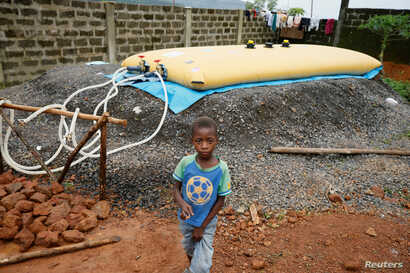 FILE - A boy walks past a water supply point at an internally displaced persons camp in Regent, Sierra Leone. Aug. 21, 2017.