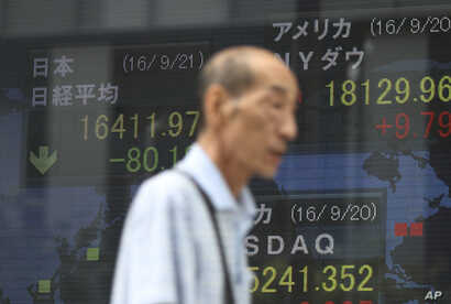 A man walks past an electronic stock board showing Japan's Nikkei 225 index, left, that fell 80.18 points or 0.5 percent to 16,411.97 at a securities firm in Tokyo, Sept. 21, 2016.