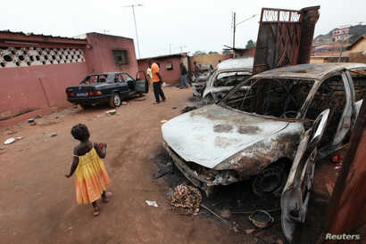 FILE - Burnt cars are seen on the yard of Soumalia Savane, a supporter of Laurent Gbagbo, Ivorian Popular Front (FPI) presidential candidate, in Gagnoa, Nov. 29, 2010.