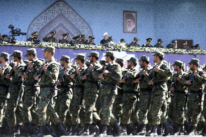 FILE - Iran's President Hassan Rouhani, top center, reviews army troops marching during the 37th anniversary of Iraq's 1980 invasion of Iran, in front of the shrine of the late revolutionary founder, Ayatollah Khomeini, just outside Tehran, Iran.