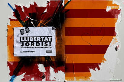 "A damaged sticker of a Spanish and Catalan flag and a placard reading ""Freedom to Jordis!"" in reference to leaders of two of the largest Catalan separatist organizations, Catalan National Assembly's Jordi Sanchez and Omnium's Jordi Cuixart, who were ..."