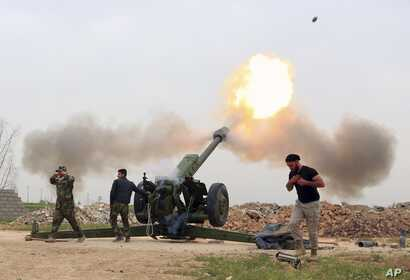 FILE - Iraqi security forces fire at Islamic State militants positions from villages south of the Islamic State group-held city of Mosul, Iraq, March 26, 2016.