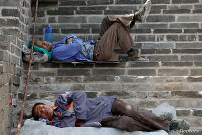 People rest after working on the reconstruction of the Jiankou section of the Great Wall, in Huairou District, north of Beijing, China, June 7, 2017.