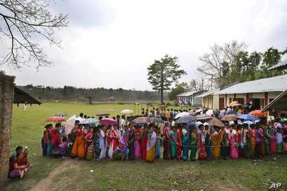 People stand in queue to cast their votes during the first phase of elections in Mandai, in the northeastern state of Tripura, India, April 7, 2014. India started the world's largest election Monday, with voters in the remote northeast making their w