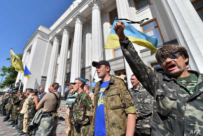 Maidan self-defense activists shout slogans in front of the Ukrainian parliament building in Kyiv on July 1, 2014, as they call for the ratification of an agreement with the European Union.