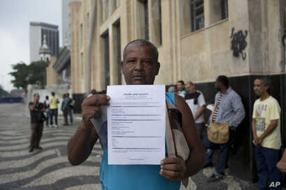 In this May 31, 2017 photo, Jose Augusto shows his resume as he stands in line in search of work at the Labor Ministry in Rio de Janeiro, Brazil.
