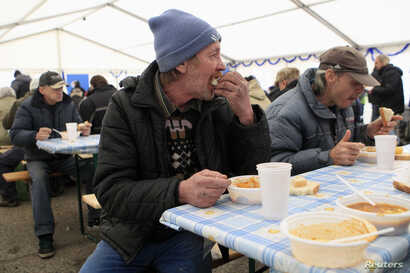 FILE - A man eats at a soup kitchen where the Hungarian Ecumenical Charity distributes free lunch to the needy ahead of Christmas in Budapest, Dec. 23, 2013.