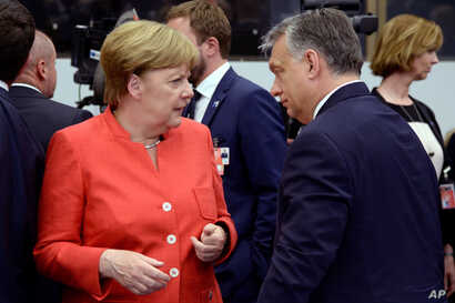 German Chancellor Angela Merkel, left, visits with Hungary's Prime Minister Viktor Orban, at the NATO headquarters in Brussels, May 25, 2017.