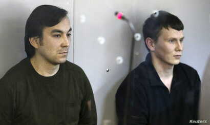 Yevgeny Yerofeyev (L) and Alexander Alexandrov, Russian servicemen arrested last May on terrorism charges related to the separatist conflict in eastern Ukraine, looks from a glass-walled cage during a court hearing in Kyiv, Ukraine, April 18, 2016.