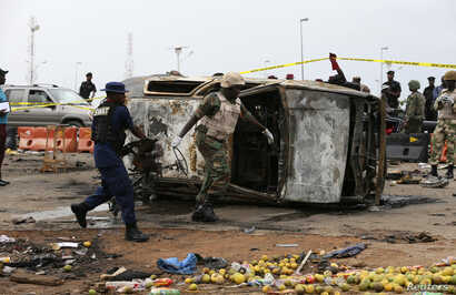A soldier and a paramilitary officer help to move part of a damaged car at the scene of a car bomb attack in Nyanya, Abuja, May 2, 2014.