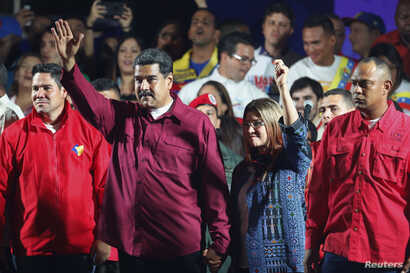 Venezuela's President Nicolas Maduro and his wife Cilia Flores wave to supporters after the National Electoral Council announced that with almost 93 percent of polling stations reporting, Maduro won nearly 68 percent of the votes in Sunday's election...