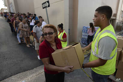 In this Dec. 21, 2017 photo, Doris Martínez receives supplies and water from municipal staff outside the City Hall in Morovis, Puerto Rico.