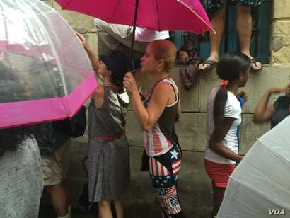 Cubans stand in the rain, hoping to catch a glimpse of U.S. President Barack Obama, after he arrived in Havana, Cuba, March 20, 2016. (V. Macchi / VOA )
