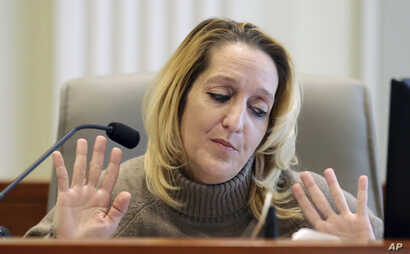 Lisa Britt throws up her hands as she answers a question by by attorney Marc Elias during the public evidentiary hearing on the 9th Congressional District investigation at the North Carolina State Bar, Feb. 18, 2019, in Raleigh, N.C.