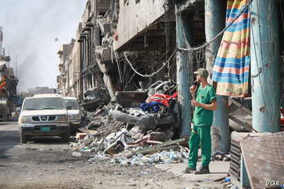 A medic takes a break outside a makeshift hospital near a battle zone in one of Mosul's many destroyed neighborhoods, July 5, 2017.