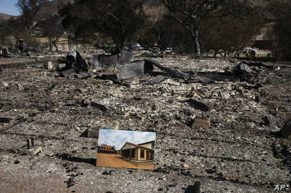 A photo of what the area looked like before is placed on the remains of a building leveled in the Woolsey Fire at decimated Paramount Ranch, during U.S. Interior Secretary Ryan Zinke's visit to the ranch, Nov. 15, 2018, in Agoura Hills, Calif.