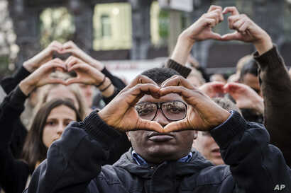 People make the shape of a heart with their hands as they stand for a moment of silence at the Bourse during the one-year anniversary for Brussels attacks victims in Brussels, March 22, 2017.