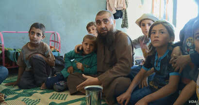 "Abu Osama, the main character in the documentary ""Of Fathers and Sons,"" is surrounded by his children in his house in northern Syria. (Kahtan Hasson for VOA)"