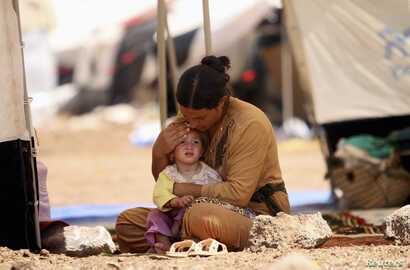 FILE - A refugee woman from the minority Yazidi sect, who fled the violence in the Iraqi town of Sinjar, sits with a child inside a tent at Nowruz refugee camp in Qamishli, northeastern Syria, Aug. 17, 2014.