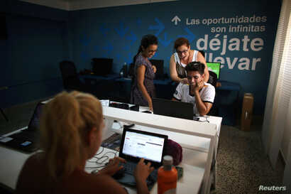 People work at the media platform OnCuba office in Havana, Cuba, Aug. 2, 2016.