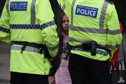 A woman and a young girl wearing a t-shirt of US singer Ariana Grande talks to police near Manchester Arena following a deadly terror attack in Manchester, northwest England on May 23, 2017.