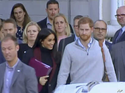 In this image made from video, Britain's Prince Harry, center right, and his wife Meghan, center left, Duke and Duchess of Sussex, approach a car at an airport in Sydney, Oct. 15, 2018.