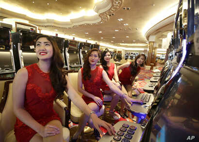FILE - Casino models pose at the slot machines during the media tour of Solaire Casino in the Philippines. Casino chips are commonly used to launder money because the exchanges quickly become anonymous.