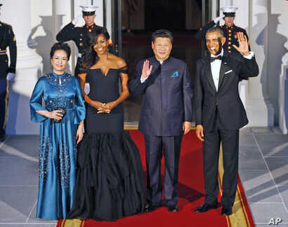 President Barack Obama and Chinese President Xi Jinping wave on the North Portico with wives Peng Liyuan and Michelle Obama as they arrive for a State Dinner at the White House in Washington, Sept. 25, 2015.
