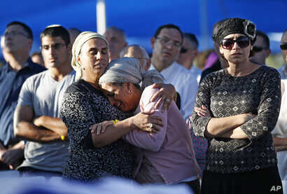 Bat-Galim Shaar, right, and Iris Yifrah, center, mothers of two of the three Israeli teens who were abducted and killed in the West Bank, mourn during the joint funeral of their sons in Modiin, July 1, 2014.