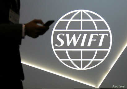 FILE - A man using a mobile phone passes the logo of global secure financial messaging services cooperative SWIFT at the SIBOS banking and financial conference in Toronto, Ontario, Oct. 19, 2017.