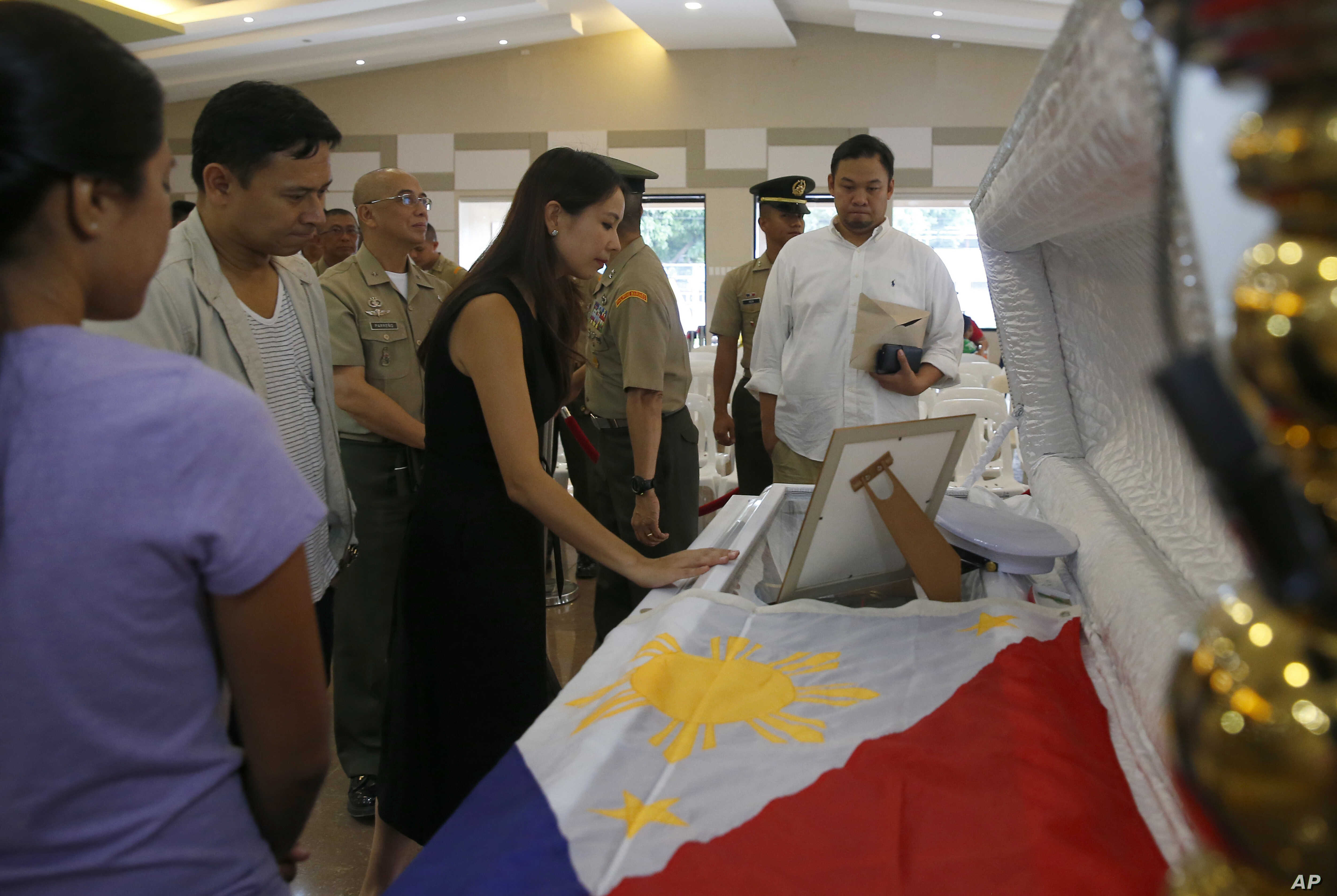 Philippine Senator Sonny Angara, second from left, and his wife, Elvira, pay their respects to Philippine Marine Pfc. Marvin Gomez, killed in the fighting with Muslim militants in Marawi City in southern Philippines, June 13, 2017 in Taguig city, eas...
