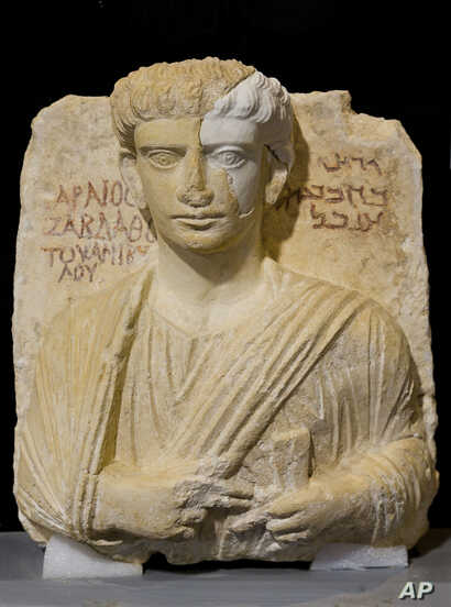 A limestone male bust dated between the 2nd and the 3rd century A.D. that was damaged during the Islamic State occupation of the Syrian city of Palmyra, is shown during a press conference in Rome, Feb. 16, 2017.
