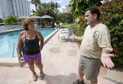 Trapper Brian Wood talks with Janet Sarno, board chairwoman at King's Point Imperial Condo, in Sunny Isles Beach, Fla., about her iguana problem, Feb. 9, 2017. Sarno hired Wood because the number of iguanas, big adults and bright green babies, hang...