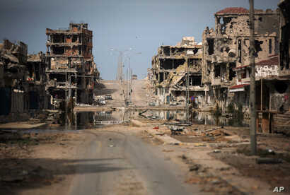 FILE - In this Oct. 22, 2011 file photo, a general view of buildings ravaged by fighting in Sirte, Libya. A leading international rights group on Wednesday released a report documenting atrocities committed by Libya's Islamic State affiliate in the c...