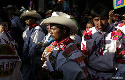 Members of the Huichol indigenous community, wearing Aztec traditional costumes, take part in a protest in Mexico City October 27, 2011.
