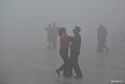 FILE - People wearing masks dance at a square in heavy smog during a polluted day in Fuyang, Anhui province, China, Jan. 3, 2017.  Beijing is concerned that the spread of unauthorized or inaccurate pollution data from popular mobile apps and handheld...