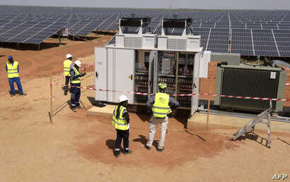 FILE - Technicians operate electrical cabinets, Oct. 22, 2016, during the opening ceremony of a new photovoltaic energy production site in Bokhol, Senegal. It was one of sub-Saharan Africa's largest solar energy projects.